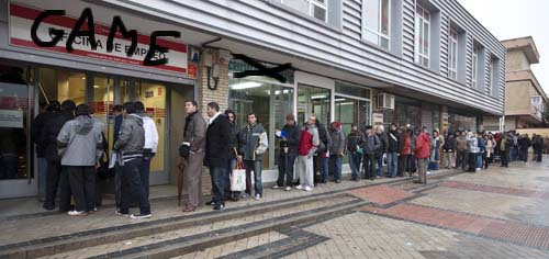People stand in a queue to enter a government job centre in Madrid